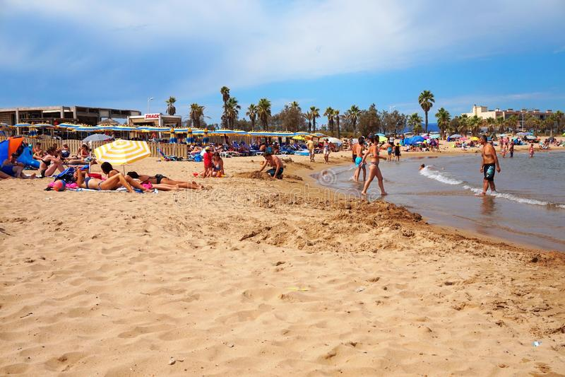 FREJUS, FRANCE - AUG 16, 2016: Beach scene with holiday makers on vacation enjoying sand and sea. royalty free stock photography