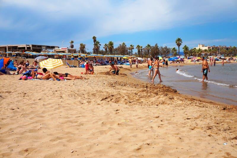 FREJUS FRANKRIKE - AUGUSTI 16, 2016: Strandplats med ferietillverkare på semester som tycker om sand och havet royaltyfri fotografi