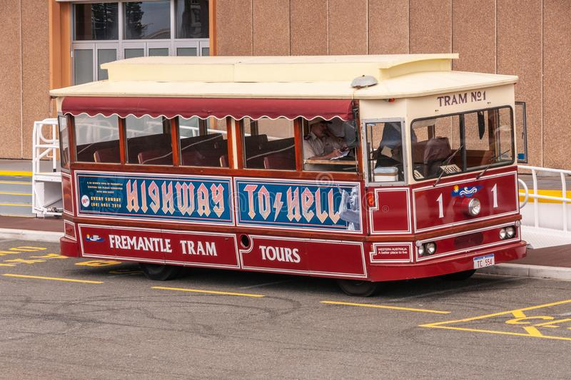 Fremantle, Australia - November 25. 2009: Maroon tour tram called Highway to Hell parked in front of borwn building waits for stock images