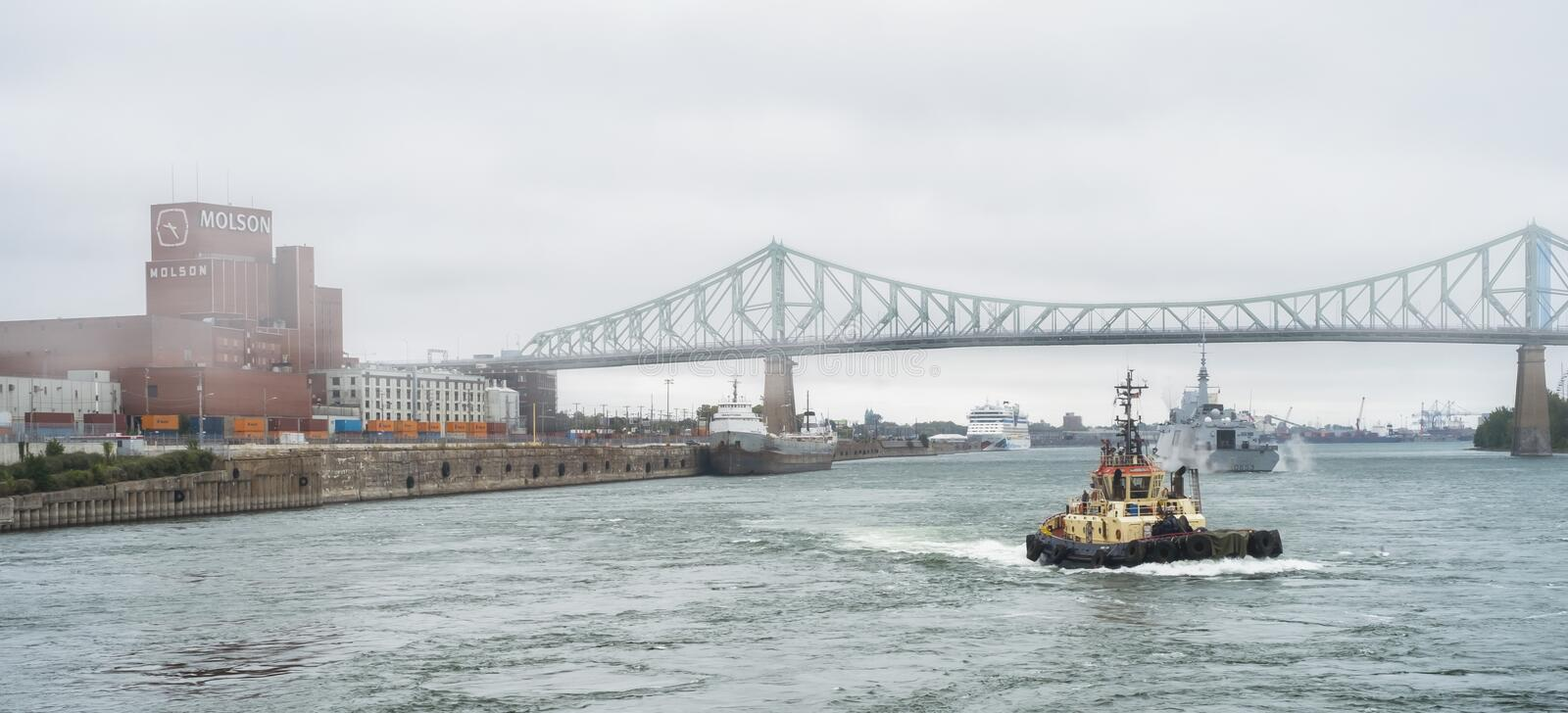 FREMM Languedoc & Svitzer Cartier tugboat. The FREMM multi-mission frigate Languedoc in fog carried out a four-day port visit in Montréal from September 24th royalty free stock image