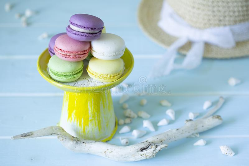 French almond cookies macaroons on yellow tray in marine decoration of shells, driftwood and sunhat stock image
