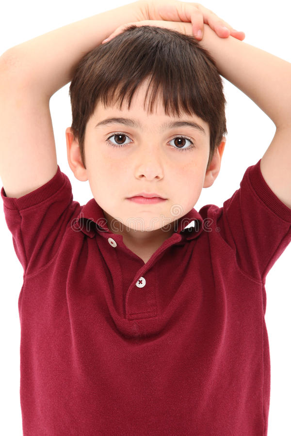 French American Boy. Attractive eight year old french american boy with serious expression, hands on head, casual shirt over white background stock photo