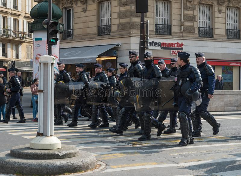 French armed forces marching in the street during yellow vests Gilets jaunes protest in Paris. Paris, France - 22nd March, 2019: French policemen and armed royalty free stock photos