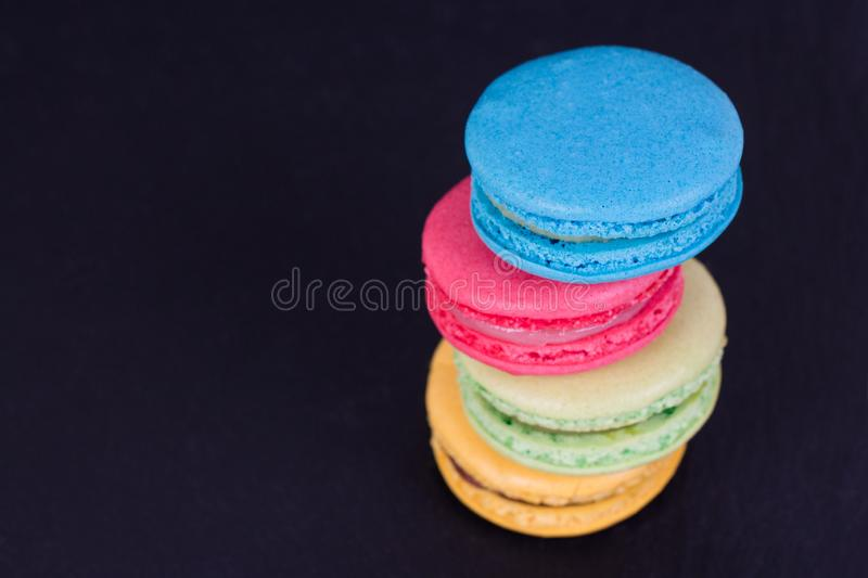 French assorted macarons cakes on a black background. Colorful Small French cakes. Top View. royalty free stock photo