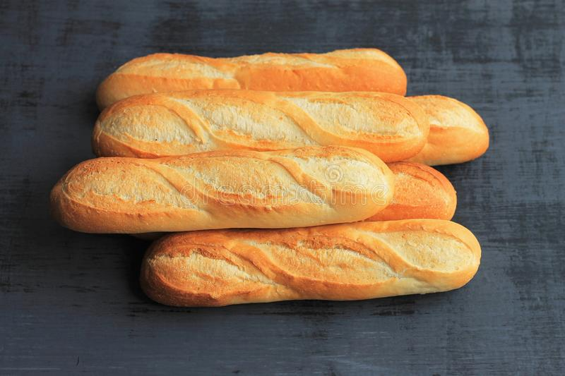 French baguettes on black wooden background, fresh bread royalty free stock photography