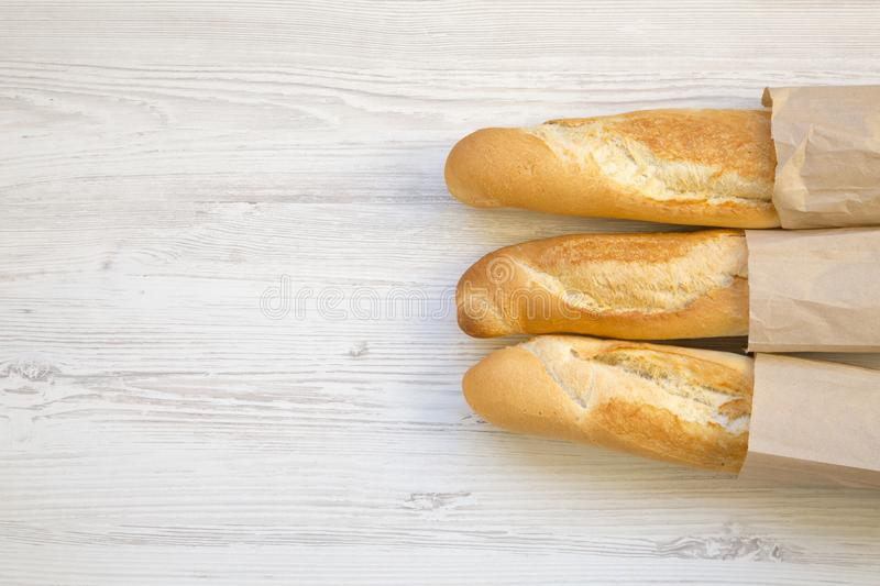 French baguettes in paper bags on white wooden table, top view. royalty free stock photo