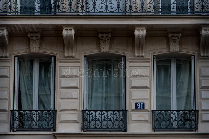 French balconies on building in Paris. Parisian apartment building with aligned windows and it`s typical French balconies. Number 21 royalty free stock photography