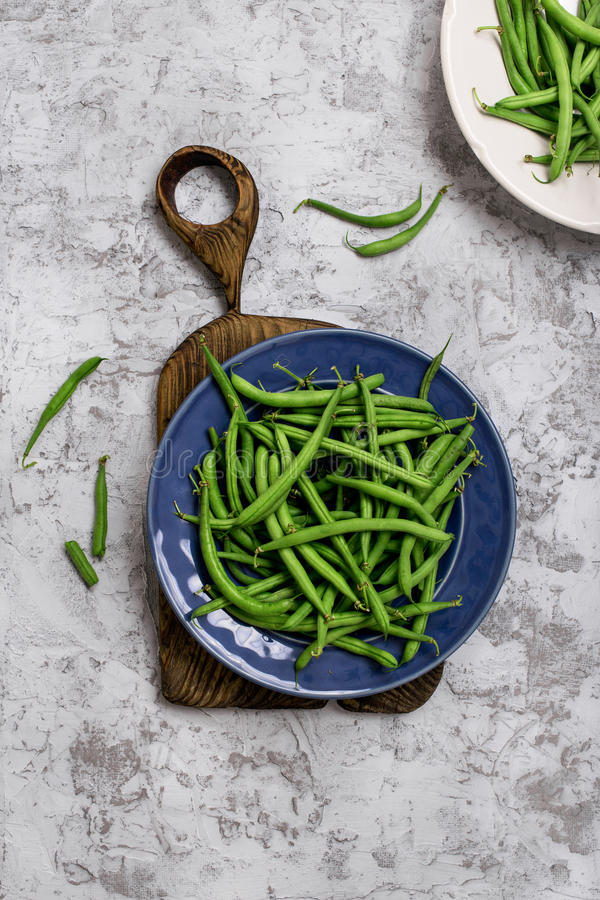 French bean in blue plate. On old wooden board on the rough light surface, top view royalty free stock photos