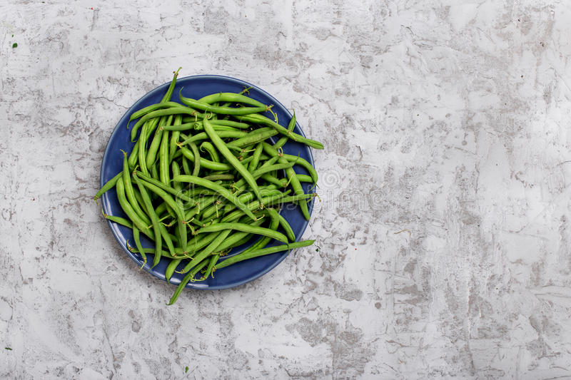 French bean in blue plate. On the rough light gray surface with copy space, top view stock photo