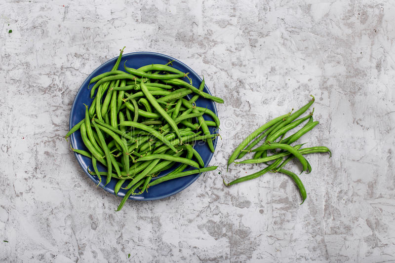 French bean in blue plate. On the rough light gray surface, top view stock images
