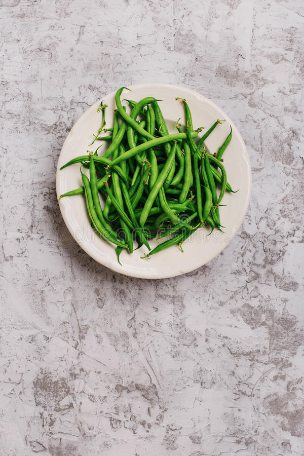 French bean in white plate. On the light surface, top view stock images