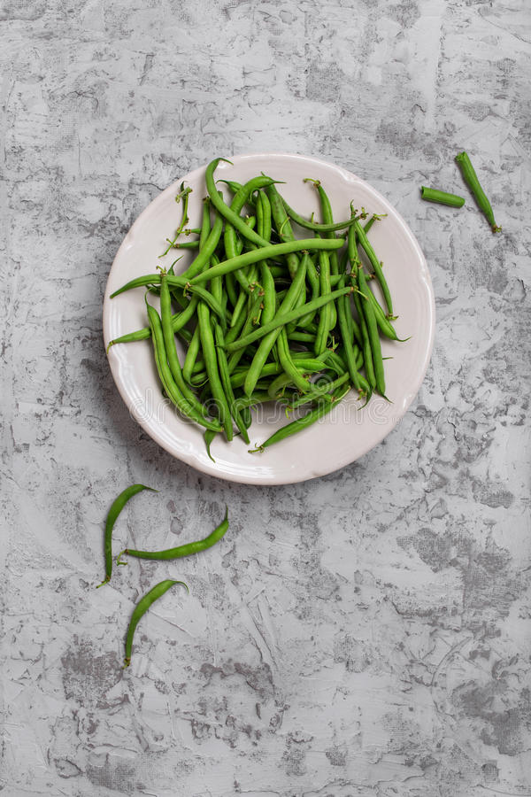 French bean in white plate. On the rough light gray surface, top view stock image