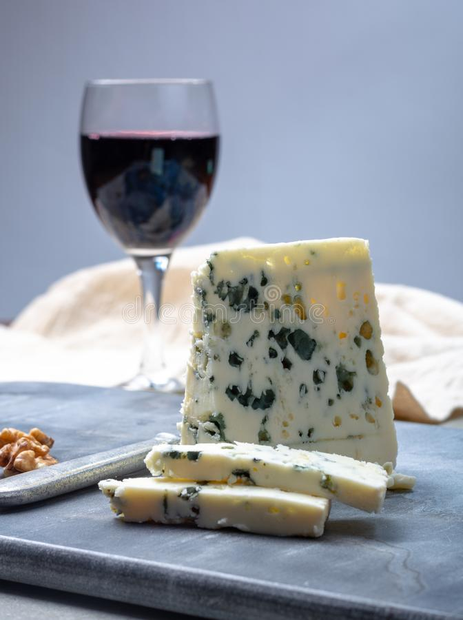 French blue cheese Roquefort, made from sheep milk in caves of Roquefort-sur-Soulzon and glas with red wine. Piece of French blue cheese Roquefort, made from stock photo