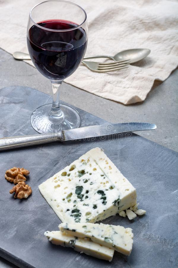 French blue cheese Roquefort, made from sheep milk in caves of Roquefort-sur-Soulzon and glas with red wine. Piece of French blue cheese Roquefort, made from royalty free stock photography