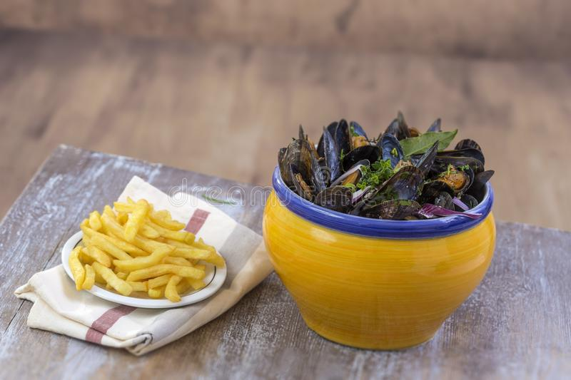 French blue mussel with herbs in a yellow bowl with french fries glass ramekin on napkin Seafood in a wooden board. French blue mussel with herbs in a yellow royalty free stock images