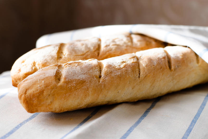 French bread. Two home-made pieces of french bread in a towel stock photos