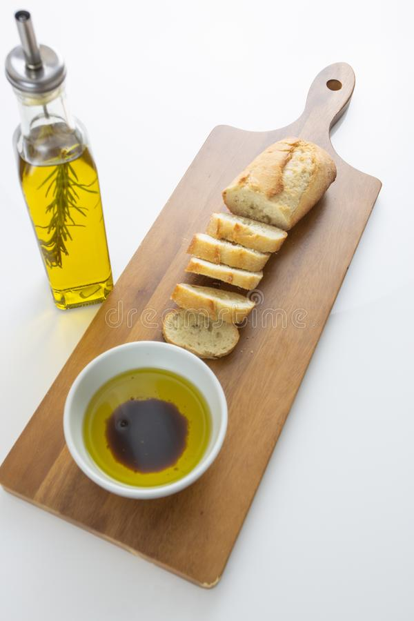 A french bread baguette sliced up on a cutting board with a bowl of olive oil with a splash of balsamic vinegar along side a bott stock photography