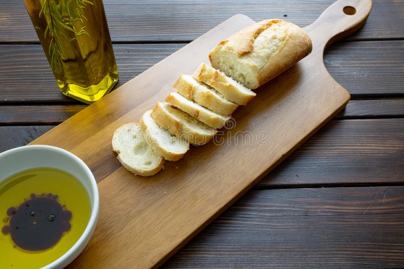 A french bread baguette sliced up on a cutting board with a bowl of olive oil with a splash of balsamic vinegar along side a bott stock photo