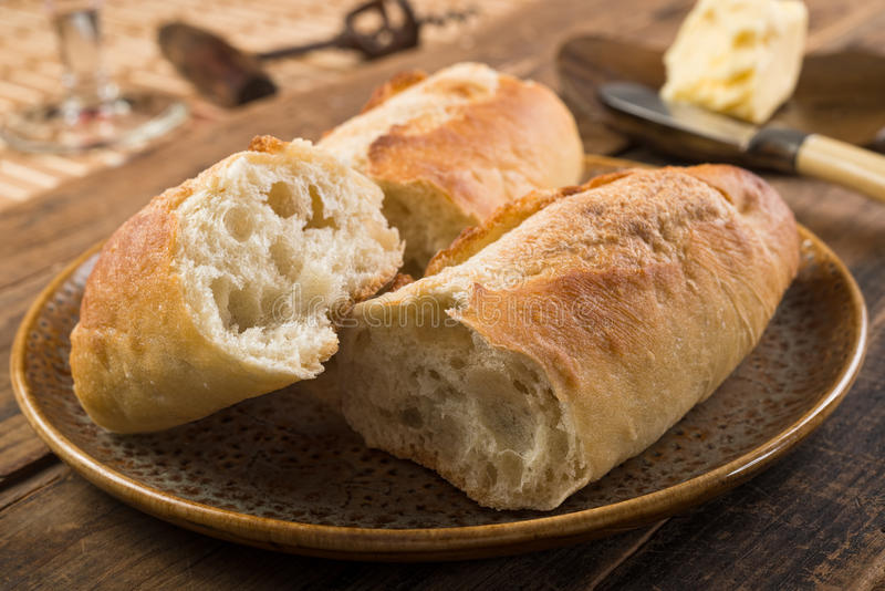 French Bread and Butter. French bread baguette and butter on a rustic wooden tabletop stock image