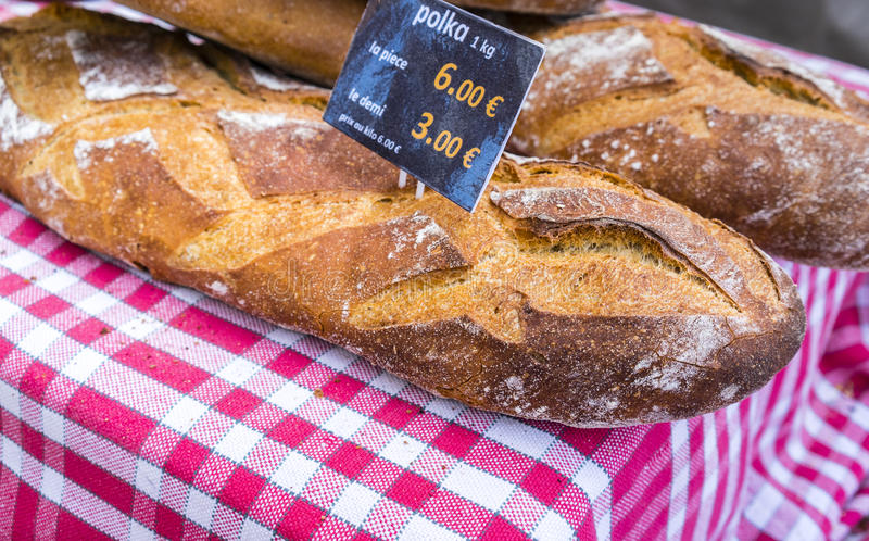 French breads with generic price signs on red checked cloth in French market. French breads in baskets with generic price signs on red checked cloth in a French stock photography