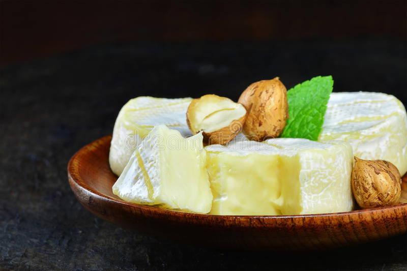 French brie cheese wheels with hazelnuts. On wooden plate stock images