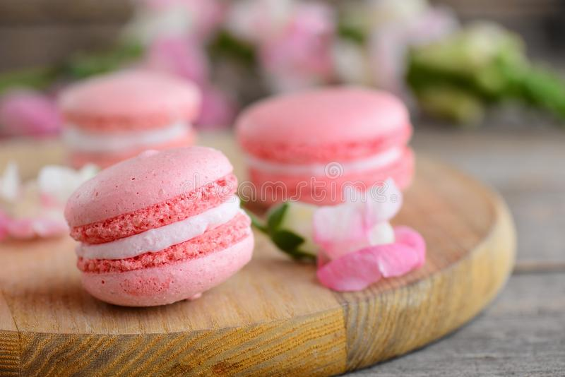 French cakes macaroons. Light pink round macaroons and flowers on a wooden board. Vintage wooden background royalty free stock photo