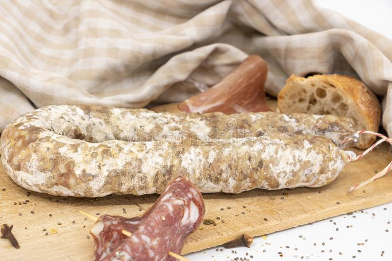 French charcuterie and baguette on a wooden cutting board. TV or tasting platter on the theme of French charcuterie, Corsican charcuterie, and cheeses royalty free stock images