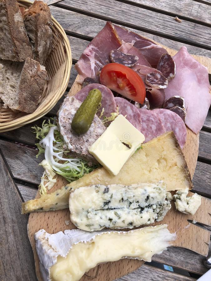 French cheese and charcuterie plate. Bread, gherkins, brie, cantal, clue cheese and meats royalty free stock photography