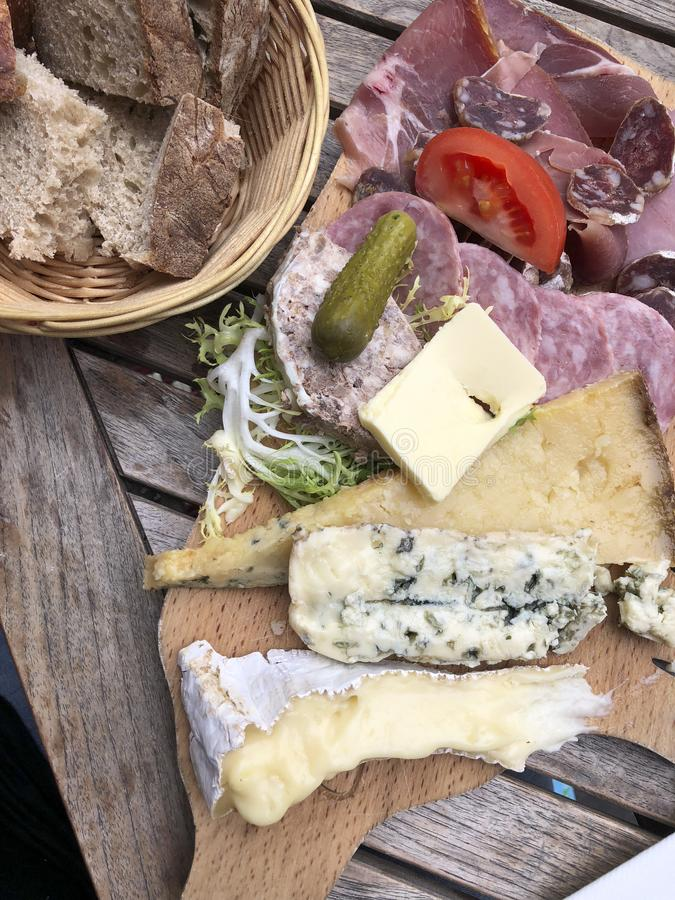 French cheese and charcuterie plate. Bread, gherkins, brie, cantal, clue cheese and meats royalty free stock image