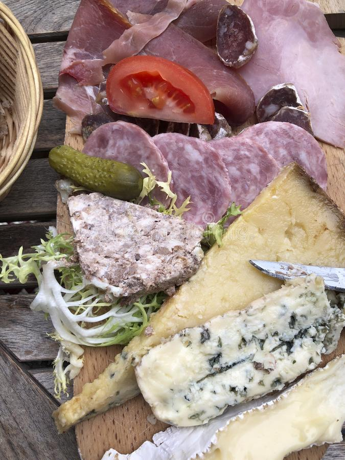 French cheese and charcuterie plate. Bread, gherkins, brie, cantal, clue cheese and meats stock photography