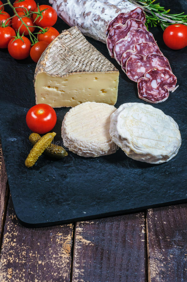 French cheese, salami, tomatoes and pickles royalty free stock photography