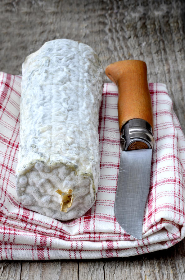 French chevre log. A french Sainte maure de Touraine goats cheese on red checked tea towel with a french pocket knife royalty free stock images