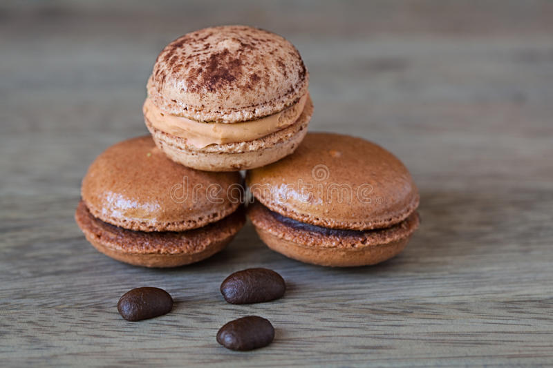 French Chocolate & Coffee Macaroons And Coffee Beans, Tasty Gormet Meringue Cookie Sandwich Cake on Vintage Wood Background royalty free stock photos