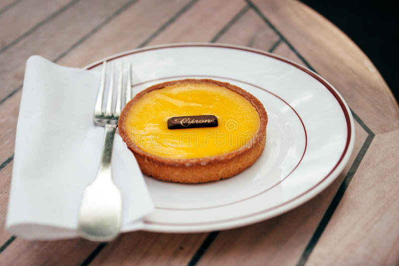 French citron pie - tarte au citron. Delicious tarte au citron (lemon tart) on plate in a Parisian cafe. Tilt-shift lens used for better image royalty free stock image