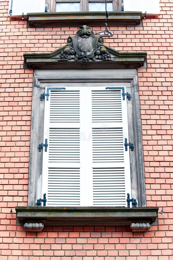 French classic style window with wooden shutters on red brick wa royalty free stock image