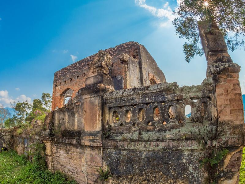 French Colonial Ruin. Muang Khoun, Laos. Ruins of French Colonial era building, villa or possibly a hospital. Red brickwork, overgrown with green vegetation royalty free stock photos