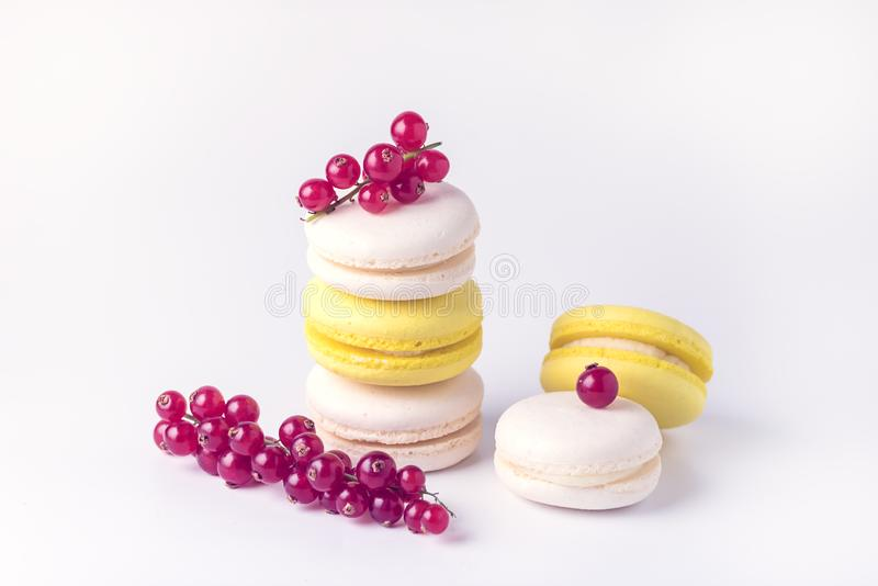 French Colorful Macarons White and Yellow Macarons on White Background with Fresh Red Currant Copy Space Horizontal Toned French. Dessert royalty free stock image