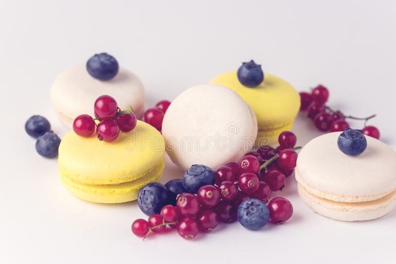 French Colorful Macarons White and Yellow Macarons on Blue Background with Fresh Red Currant Copy Space Horizontal French Dessert. Toned royalty free stock photo