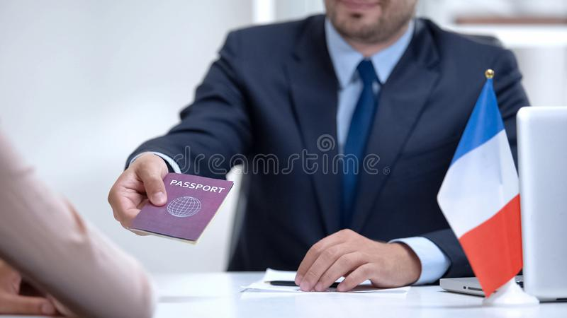 French consular officer giving passport to woman, refugee visa, asylum status. Stock photo royalty free stock images