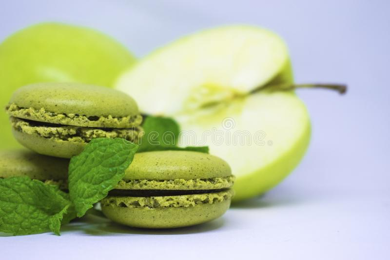 French macaroons and green apple, white background royalty free stock photography