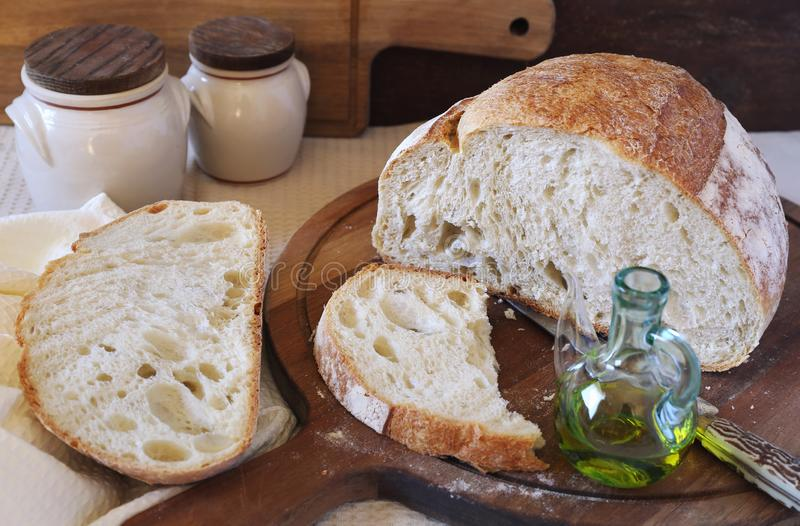 French country bread and olive oil, rustic style. French country bread and olive oil on wooden chopping board, rustic style stock images
