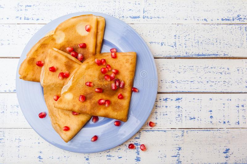 French crepes with garnet and nuts on blue plate over white back stock image