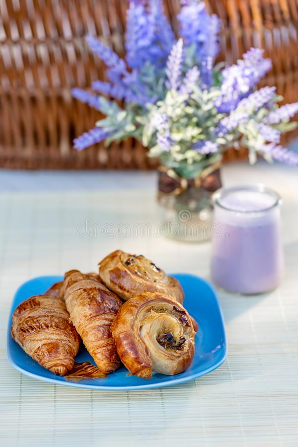 French croissants, buns with raisins and blueberry yogurt in glass jars on a table. stock image