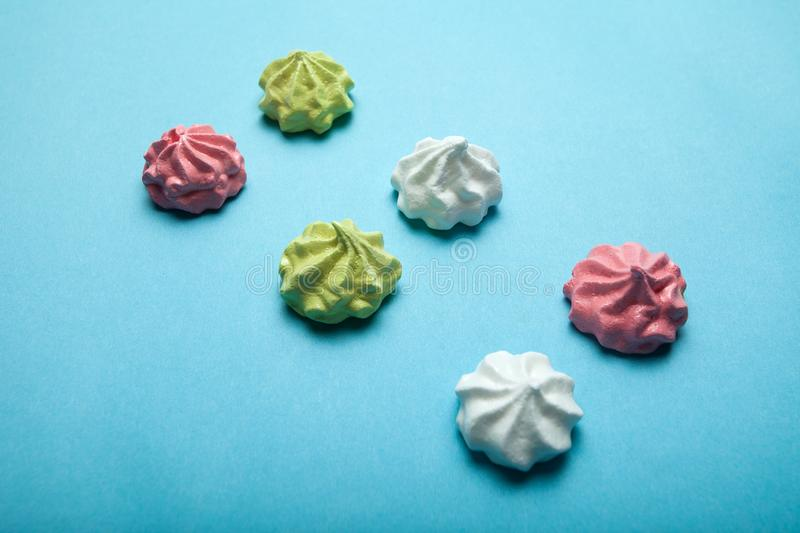 French delightful multi-colored meringue on a blue background royalty free stock photography