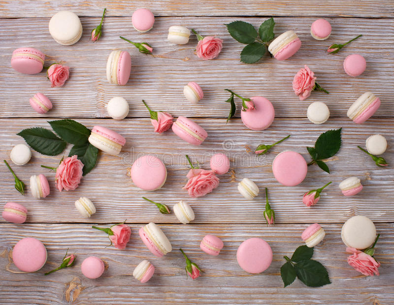 French dessert macarons pattern with rose flower. Pink and white almond cookie. Flat lay stock photo