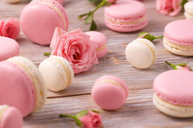 French dessert macarons with rose flowers. French dessert macarons with roses on buckground. Pink and white macaron, big and small macarons. Selective focus on stock photos