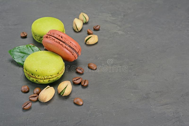French dessert. Sweet chocolate and pistachio macaroons or macarons with coffee beans and nuts royalty free stock image