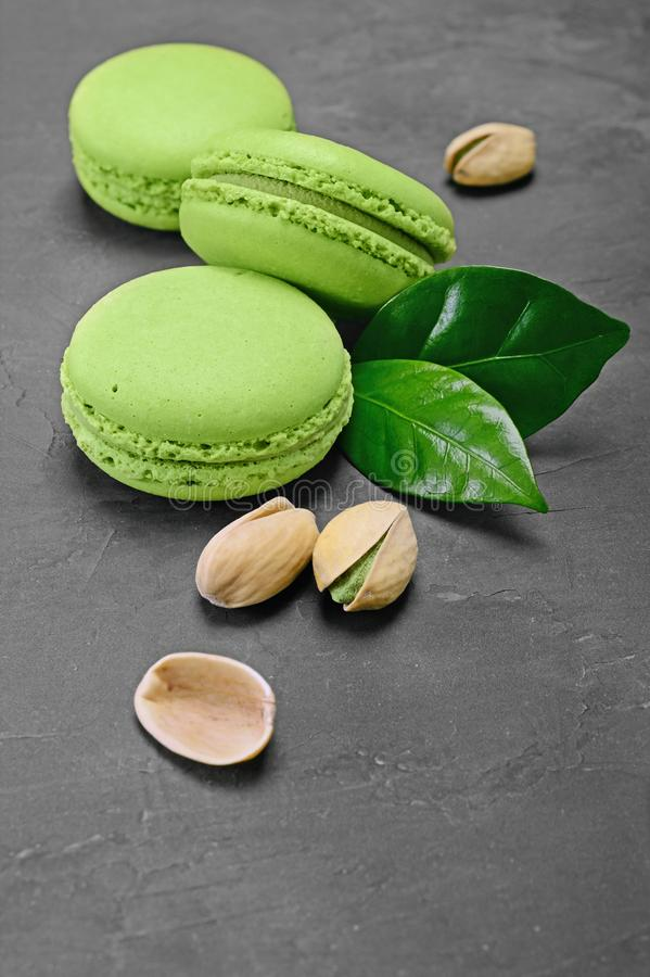French dessert. Sweet green pistachio flavor macaroons or macarons with nuts and leaves stock images