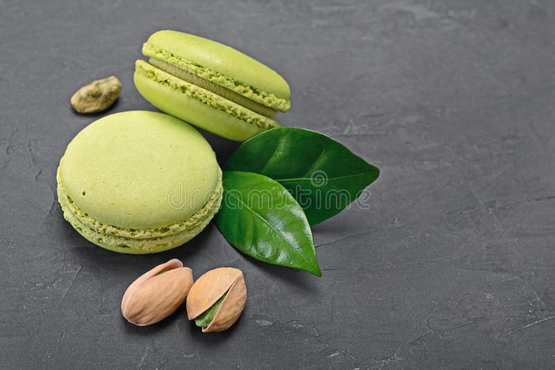 French dessert. Sweet green pistachio flavor macaroons or macarons with nuts and leaves royalty free stock image