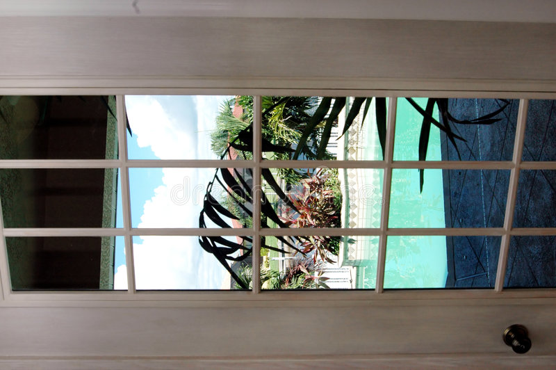 French door. White washed french door looking out to tropical pool patio view stock images